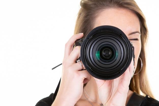 Молодая блондинка фотограф берет фотографию, изолированные на белом