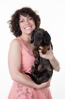 笑顔の女性と白で隔離される犬の優しい抱擁