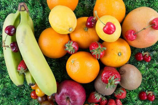 Ассортимент экзотических фруктов на деревянный стол на зеленый