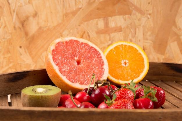 Клубника, виноград, киви, апельсин и грейпфрут на тарелку.