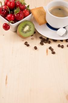 ホットコーヒーとおいしいケーキ、フルーツの木製テーブル