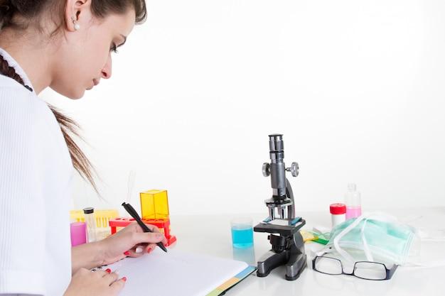 顕微鏡を使用して、メモ帳で書く女性の科学者