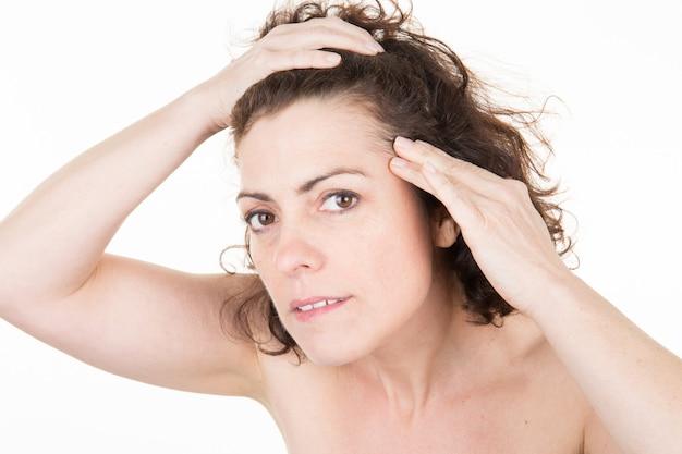 女性は彼女の頭皮を鏡を見ながら白い髪をチェックしています