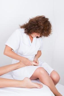 巻き毛の女性による足裏マッサージ