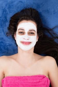 彼女の顔に粘土マスクを持つ美しい女性