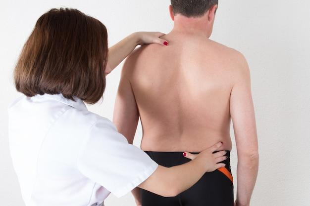 理学療法士の女性医師が患者の背中を調べる