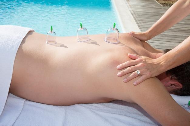 Многократные вакуумные чашки медицинской баночной терапии на спине человека