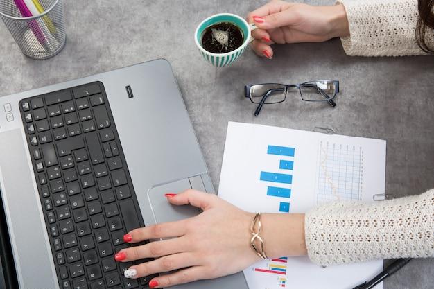 Финансовый отчет с ноутбуком бизнес женской руки и пить кофе