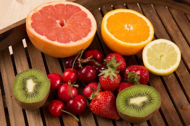 Клубника, вишня, виноград, киви, апельсин и грейпфрут на тарелку. блюдо с фруктами.