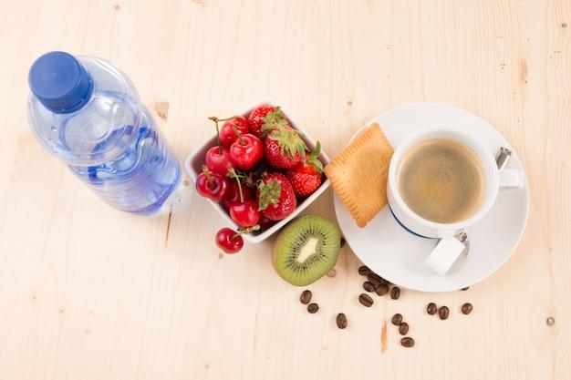 Кофе, вода, пирожные и фрукты на деревянном столе