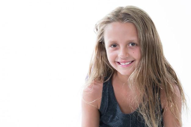 白で隔離される長い毛を持つスタジオで幸せな笑顔の美しい少女の肖像画
