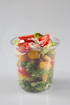 Небольшой свежий салат в пластиковом контейнере или закусочную тележку