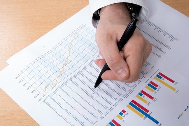 Финансовые документы крупным планом с ручкой и рукой деловых людей