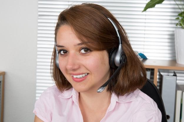 オフィスのヘッドセットで陽気なサポート電話オペレーター