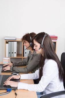 幸せな笑顔の女性顧客の肖像画は、職場での電話オペレーターをサポートします。
