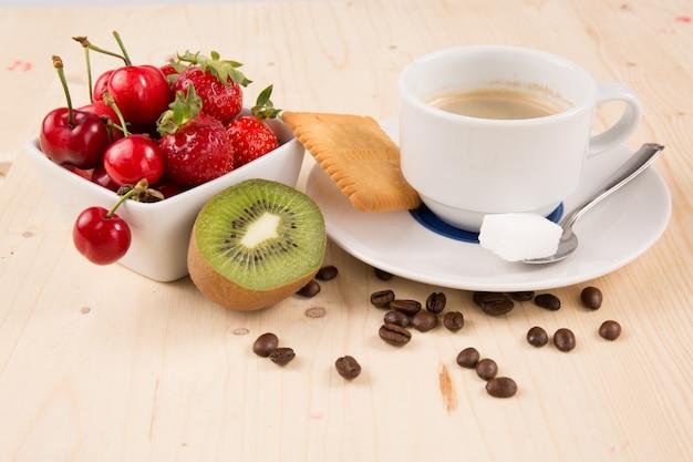 ホットコーヒー、ケーキ、チェリー、イチゴ、木製のテーブルの上