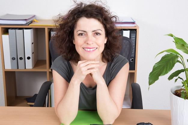 Улыбающаяся женщина в ярком офисе сидит за столом