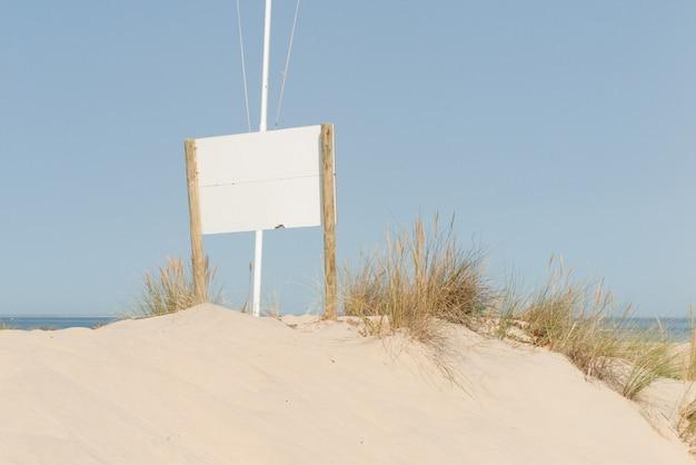 暖かい日光の下で白い砂浜に空のブラックボード
