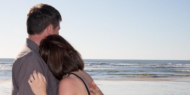 ビーチで美しい夕日を楽しんで幸せなロマンチックな中年夫婦