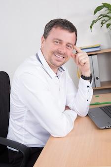 デスクトップコンピューターの前に座っている陽気な男
