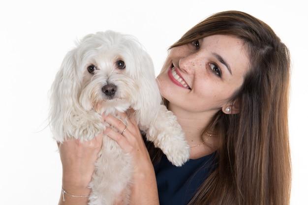 Молодая женщина, с белой собакой, выглядит счастливой улыбкой