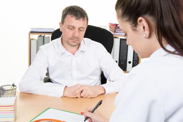 Женщина-врач обсуждает диагноз с пациентом в офисе