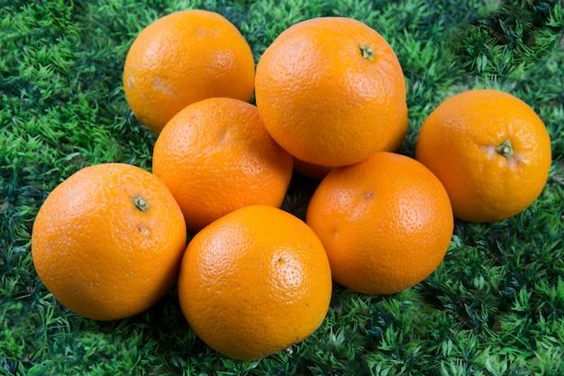テーブルの緑の草に新鮮なオレンジ色の果物