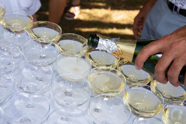 Официант делает шампанское на открытом воздухе в бокалах