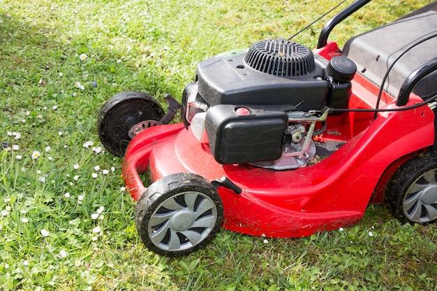 ガソリンエンジンを搭載した芝刈り機が芝生を切る