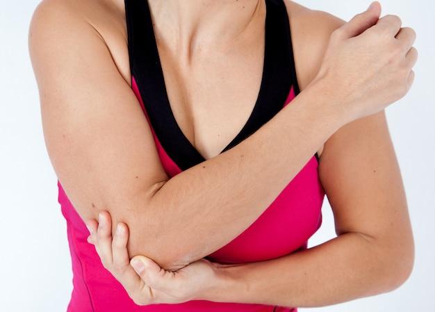 彼の肘-スポーツ傷害の痛みを持つ若い女性