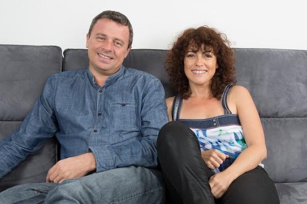 ソファーに座ってリラックスした陽気な幸せなカップル