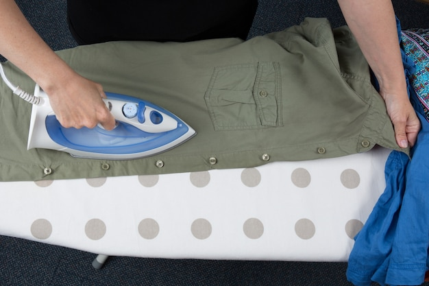 Счастливая женщина гладит мужскую рубашку с электрическим утюгом