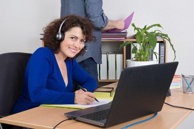 オフィスでヘッドセットで魅力的な笑顔陽気なサポート電話オペレーター