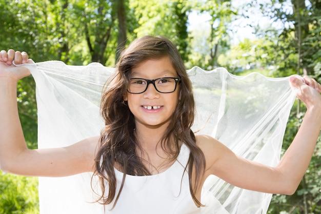 Девушка с длинными волосами в очках играет с вуалью на улице