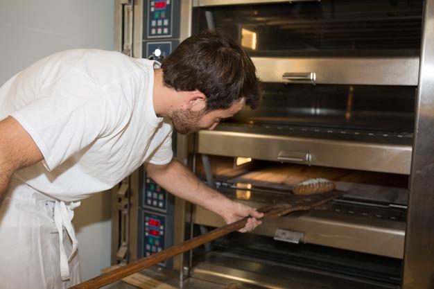 焼きたてのパンをシャベルで取り出す制服のパン屋