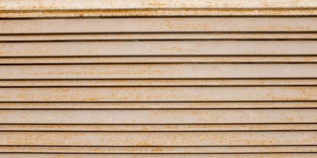 Старая металлическая дверь коричневого цвета, оранжевая стена, ржавый и окисленный металлический фон