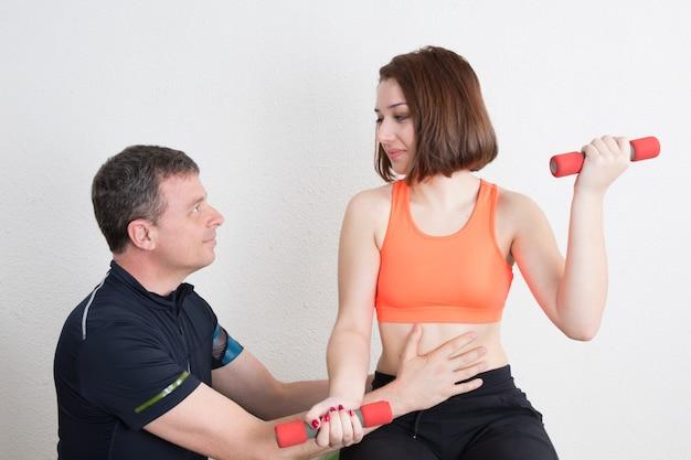 Женщина делает упражнения с помощью тренажерного зала