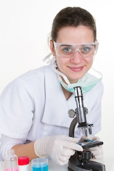 Привлекательный молодой исследователь, глядя в микроскоп лаборатории.
