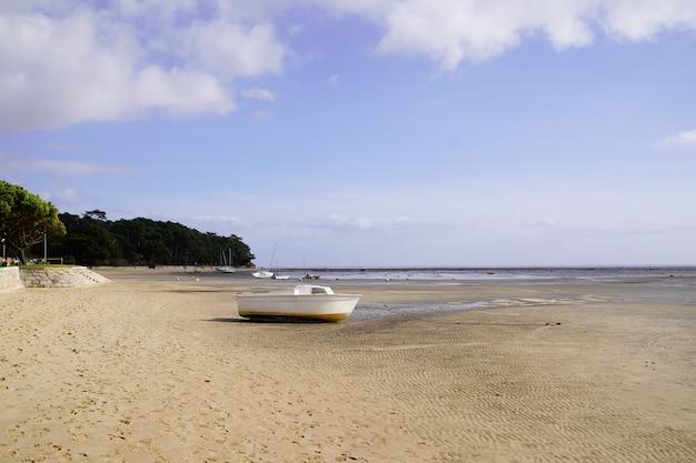 Маленькая лодка на песчаном пляже во время отлива в аресе в аркашон бэй жиронда департамент франция
