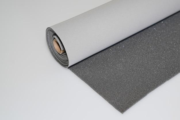 Двухцветный серый и темно-серый текстильный рулон на белом фоне