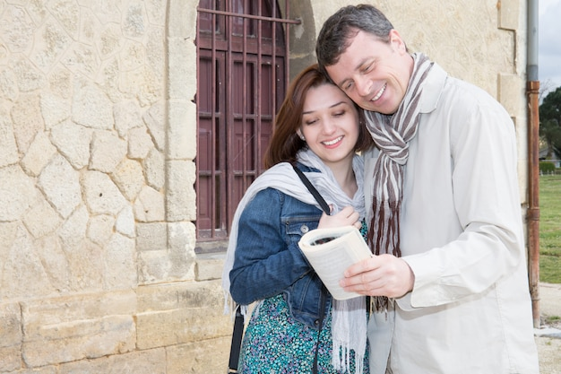 Счастливая пара с картой в туристическом книжном путешествии посещая город