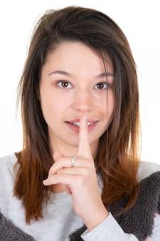 Молодая женщина просит тишины или секретности с пальцем на губах