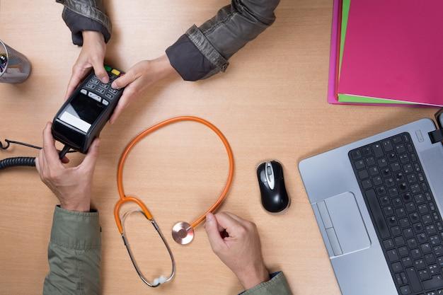医者は机に座って、患者を受信するラップトップに取り組んで