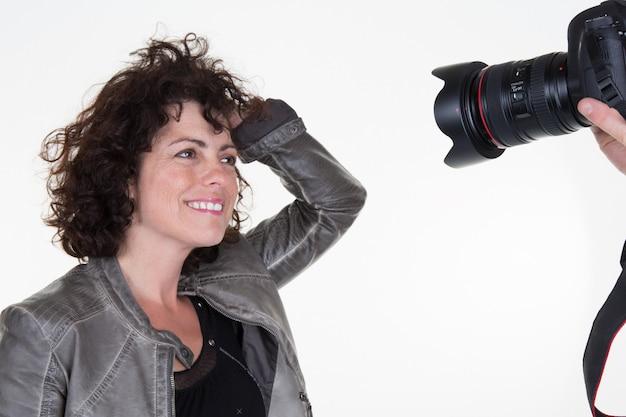 Руки фотографа, держа камеру и перед женщиной