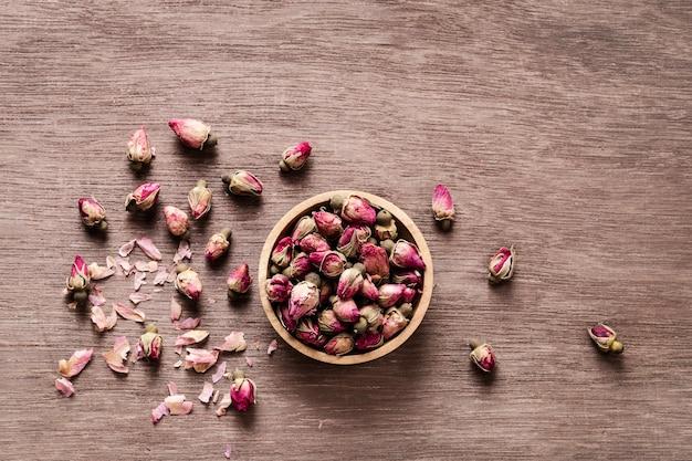 Розовые красные сушеные бутоны роз в деревянной миске с лепестками