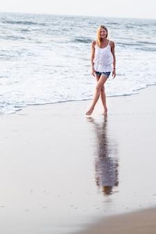 アジアの砂の熱帯のビーチで魅力的な幸せな成熟した観光客女性。