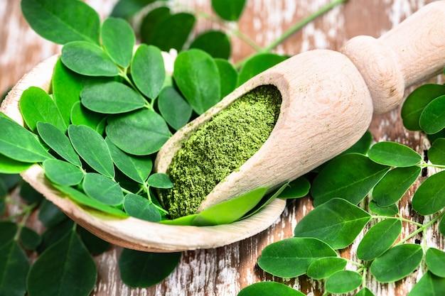 Порошок моринги в деревянной ложке с оригинальными свежими листьями моринги на деревянном столе.