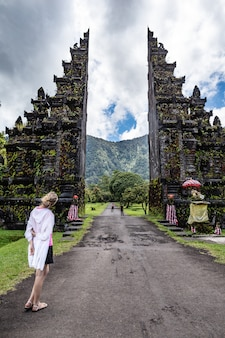 観光客の女性は伝統的なバリのヒンズー教の門を探しています