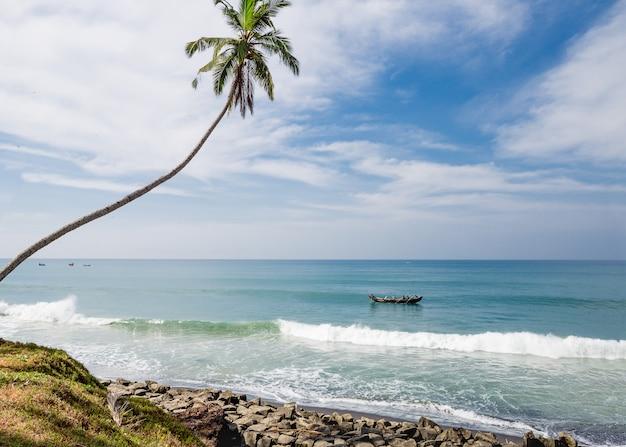 漁師船とインドのオダヤムビーチでヤシの木と海の景色