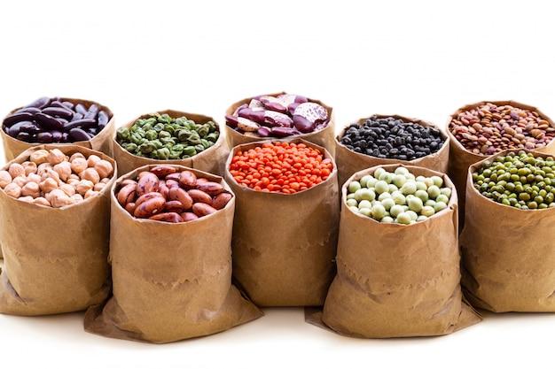 白い背景に分離された紙袋バッグでインドのマメ科植物の様々な品揃えセット。